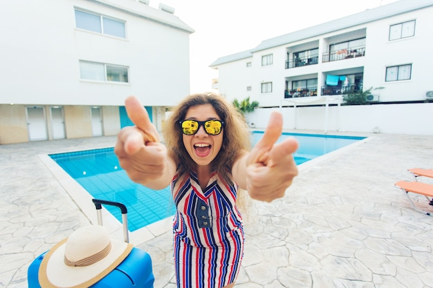 Fille heureuse montrant les pouces vers le haut pendant les vacances d'été contre la piscine, robe rayée habillée et lunettes de soleil