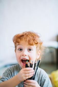 Fille heureuse, montrant des tas de crayons