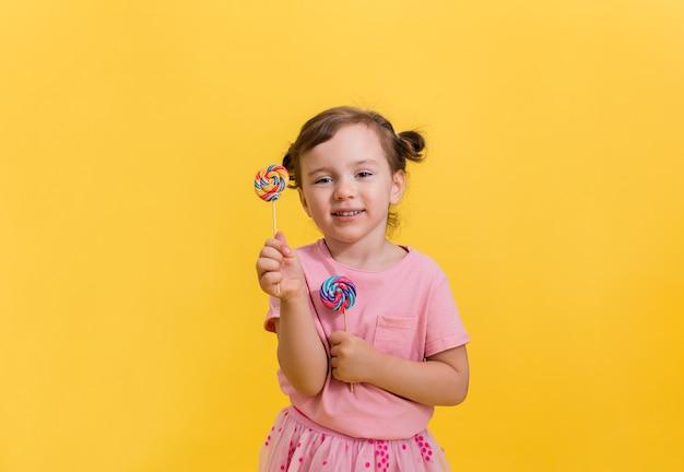 Fille heureuse avec des nattes sur jaune tenant des sucettes sur un bâton
