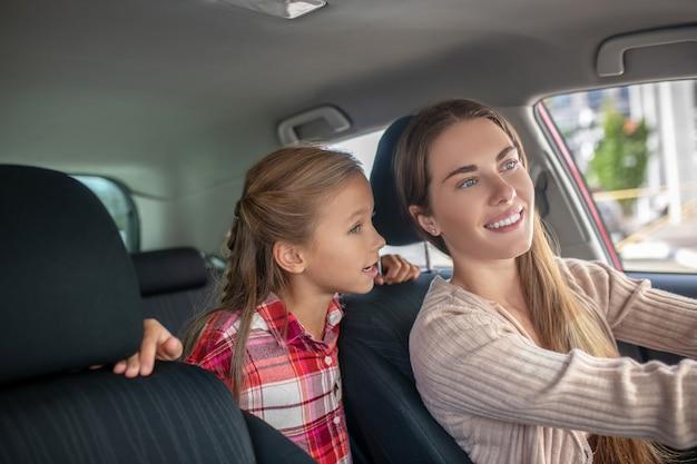 Fille heureuse de parler à sa mère de la banquette arrière de la voiture