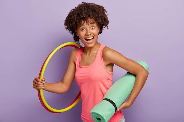 Une fille heureuse à la peau sombre porte un tapis turquoise, deux cerceaux, fait de l'exercice dans une atmosphère domestique, fait du sport pour être en bonne santé et en forme, se tient à l'intérieur contre un mur violet. concept sportif