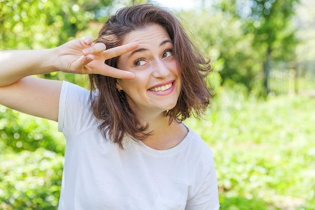 Fille heureuse en plein air. belle jeune femme brune aux cheveux bruns montrant la paix, la victoire ou deux signe sur fond vert parc ou jardin.