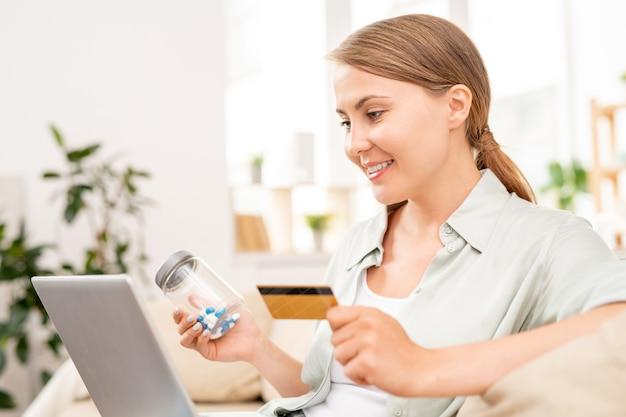 Fille heureuse avec pot de pilules et carte en plastique à la recherche d'une pharmacie en ligne pour la médecine à loisir