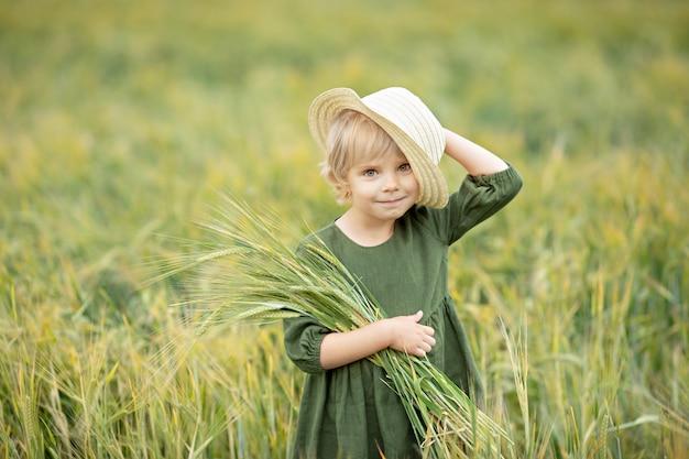Fille heureuse qui marche dans le blé doré, profitant de la vie sur le terrain. nature beauté et champ de blé. mode de vie familial en plein air. concept de liberté. jolie petite fille dans le champ de l'été