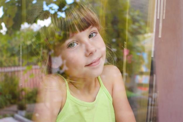 Fille heureuse regardant par la fenêtre