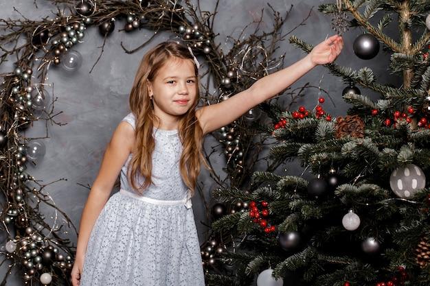 Fille heureuse en robe bleue décorant le sapin de noël.