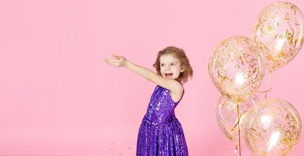 Fille heureuse en robe rose célébrant