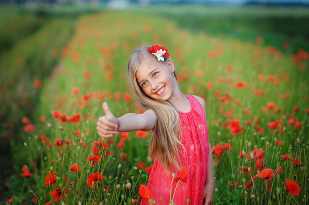 Fille heureuse en robe rouge sur un champ de coquelicot
