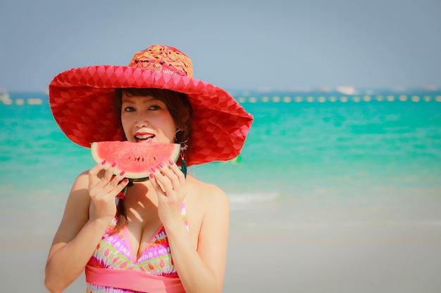Fille heureuse s'amusant sur la plage et mangeant de la pastèque, concept de vacances d'été