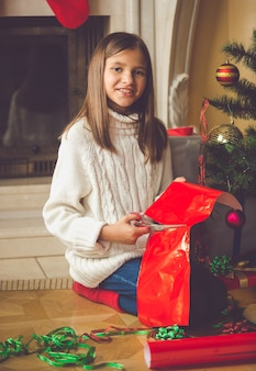 Fille heureuse s'asseyant à la cheminée et emballant des cadeaux de noël