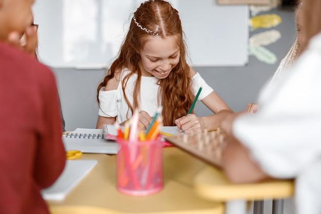 Fille heureuse s'asseyant à la table et écrivant dans un cahier