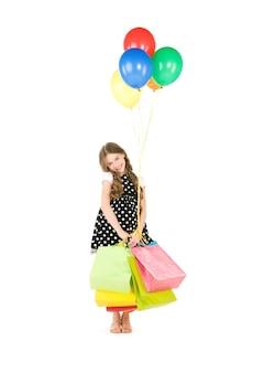 Fille heureuse avec des sacs à provisions et des ballons sur un mur blanc