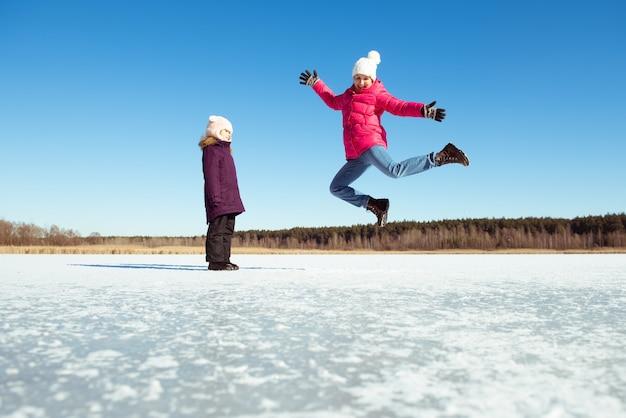 Fille heureuse sautant par-dessus le ciel bleu et fond de neige