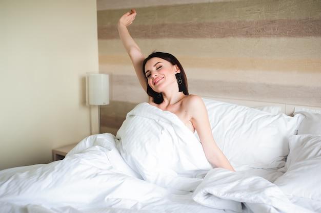 Fille heureuse se réveiller étirement des bras sur le lit le matin.