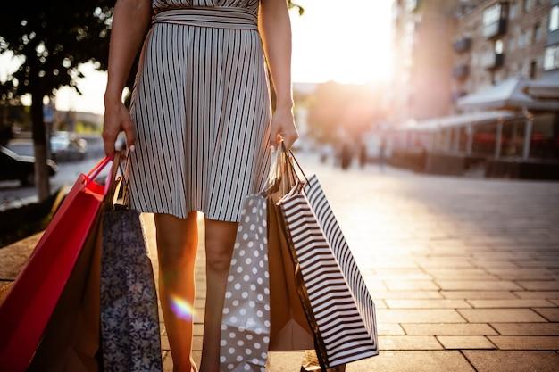 Fille heureuse se tient près de la boutique de la boutique tenant quelques sacs avec des achats.