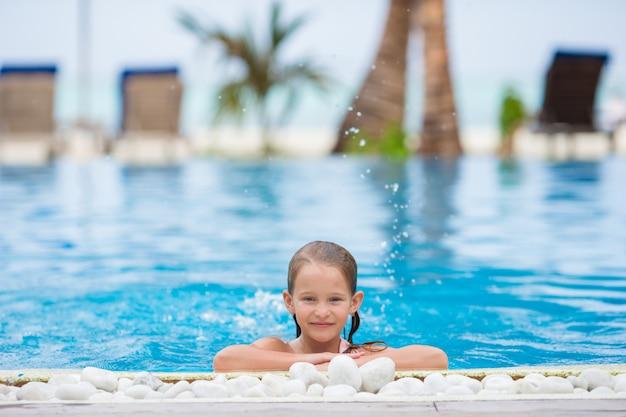 Fille heureuse souriante dans la piscine extérieure