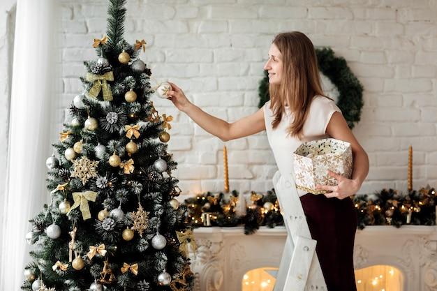 Une fille heureuse souriante décore le sapin de noël sur le fond de mur de briques blanches dans le studio. il y a une cheminée et de nombreux cadeaux.