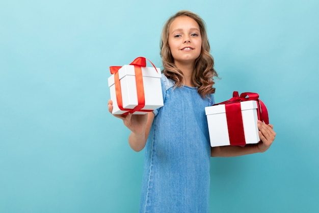 Fille heureuse surprise avec deux boîtes de cadeaux avec un ruban rouge sur un bleu clair