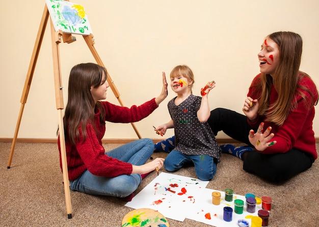 Fille heureuse avec le syndrome de down et femme peinture