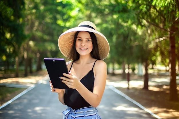 Fille heureuse avec une tablette à la main et portant un chapeau, l'activité commerciale et sociale sur internet étant dans la nature.