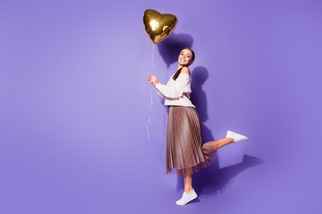 Fille heureuse tenant dans la main ballon d'hélium posant