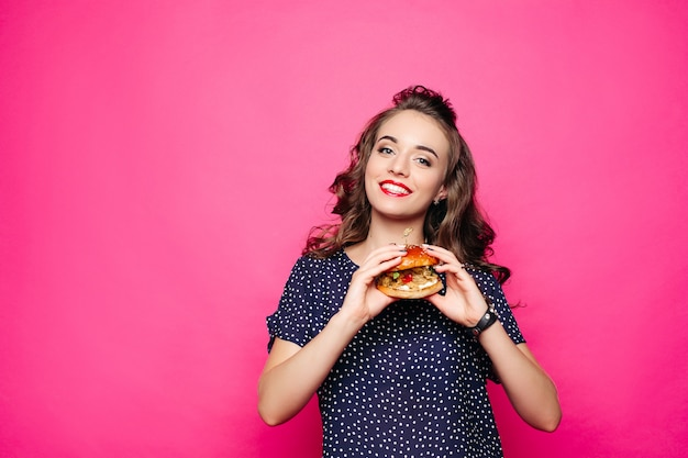 Fille heureuse tenant un hamburger.