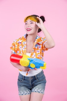 Fille heureuse tenant un pistolet à eau de fond rose.