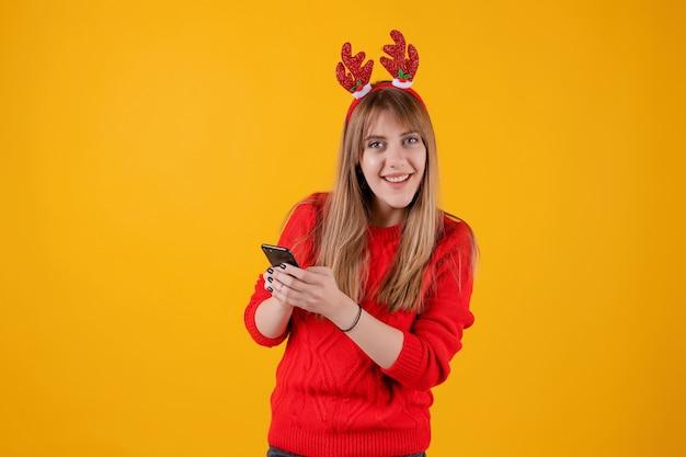 Fille heureuse, tenant un smartphone dans les mains portant un cerceau de noël drôle