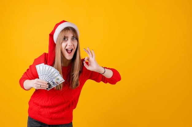 Fille heureuse, tenue, billets banque, dans main, à, geste ok, porter, noël bonnet