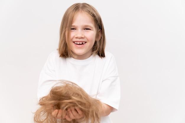 Une fille heureuse tient dans les mains les cheveux coupés après avoir coupé sur un fond blanc. signifie prendre soin des cheveux des enfants. salon de beauté pour enfants.