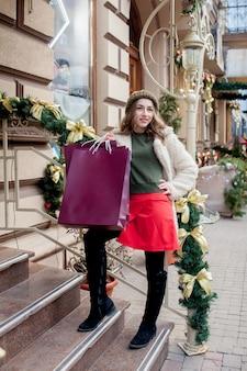 Une fille heureuse tient des sacs en papier avec le symbole de la vente dans les magasins avec des ventes à noël