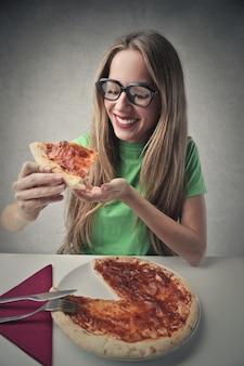 Fille heureuse en train de manger une pizza