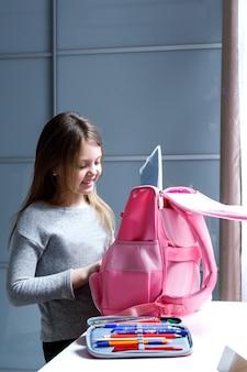 Une fille heureuse va à l'école et ramasse un sac à dos à la maison