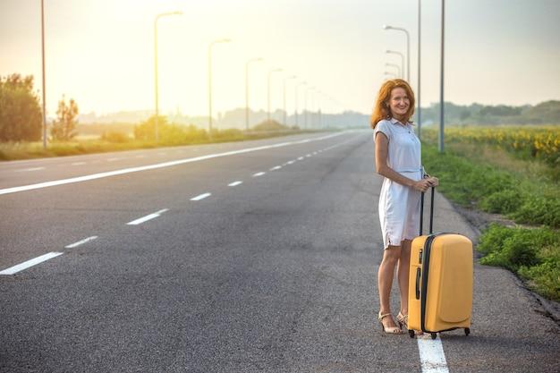 La fille heureuse et la valise jaune sur la route