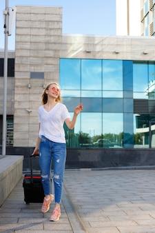 Une fille heureuse avec une valise pour voyager passe l'été à l'aéroport