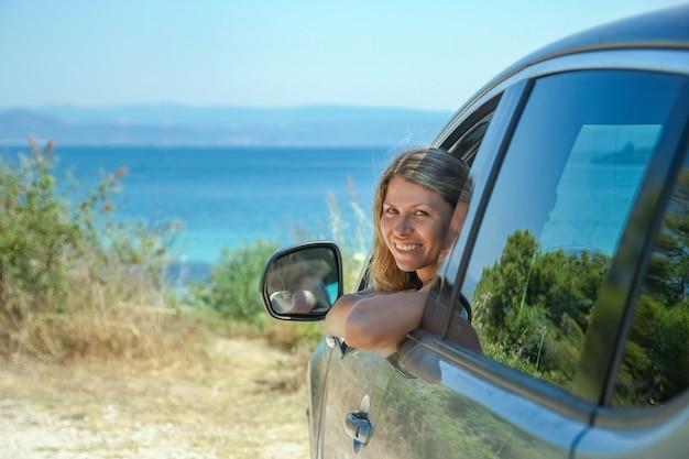 Fille heureuse de voiture au bord de la mer
