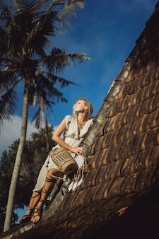 Fille hippie aux longs cheveux blonds dans une robe sur le toit.