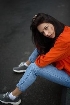 Fille hippie belle femme se promène dans la ville dans une veste rouge à la mode