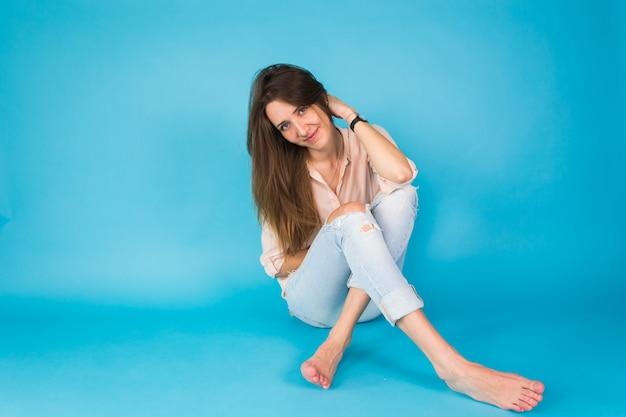 Fille de hipster assis sur le sol contre le bleu