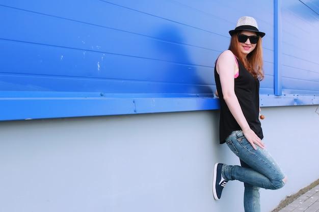 Fille hipster au mur bleu