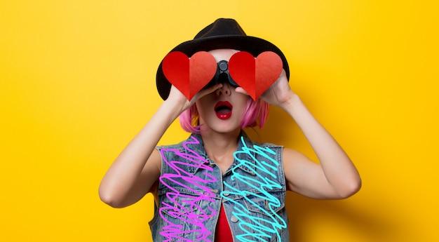 Fille hipster avec une coiffure rose avec des jumelles