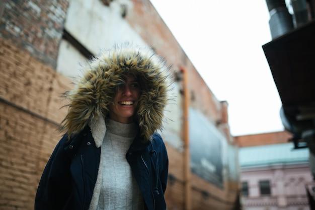 Fille de hipster dans une capuche avec de la fourrure portant une veste bleu foncé