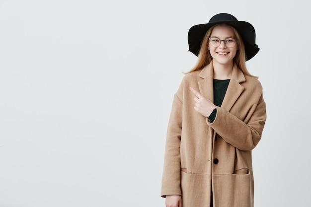 Une fille hipster excitée voit quelque chose d'incroyable, indique avec l'index à l'espace de copie pour votre texte publicitaire ou promotionnel. surpris jeune femme élégante en lunettes pointe à distance