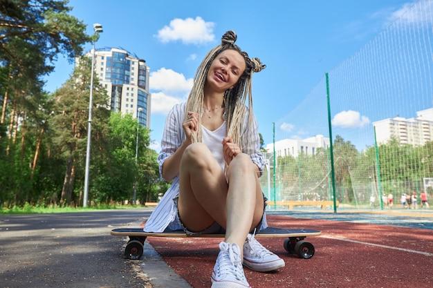 Une fille hipster moderne est assise sur un longboard sourit et montre sa langue en regardant directement l'appareil photo photographie de sport photo de haute qualité