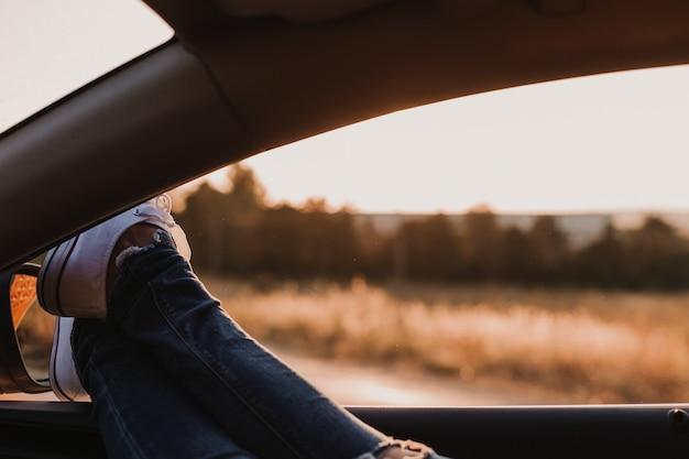 Fille hipster moderne méconnaissable se détendre dans une voiture. pieds devant la fenêtre au coucher du soleil. concept de voyage