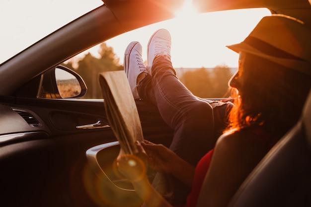 Fille hipster moderne se détendre dans une voiture et lire une carte. pieds devant la fenêtre au coucher du soleil. concept de voyage