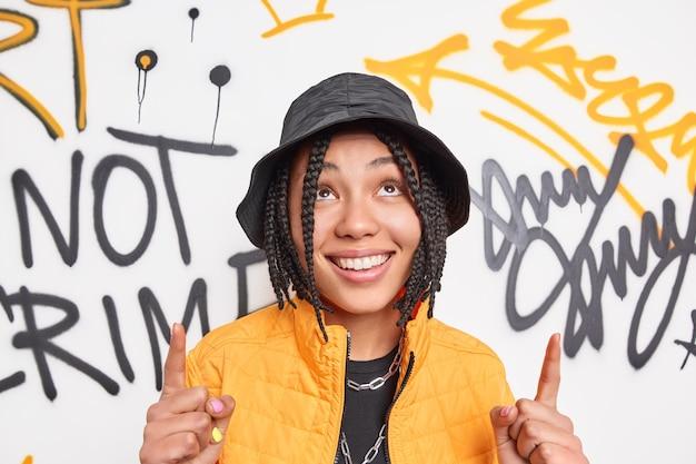 Fille hipster positive avec des tresses sourit largement pointe l'index au-dessus de la tête vêtue de vêtements à la mode démontre quelque chose contre le mur de graffitis appartient à la sous-culture de la jeunesse