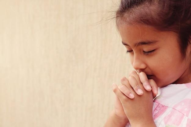 Fille hispanique enfant priant avec les yeux fermés