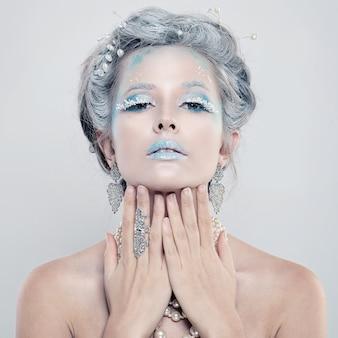 Fille d'hiver. belle femme modèle avec bijoux en argent et maquillage de neige