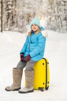 Une fille en hiver en bottes de feutre est assise sur une valise un jour de neige glaciale.